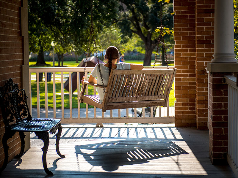 A young woman sits on a swing on Cudd Hall. Her back is to the camera and she appears to be reading a book.
